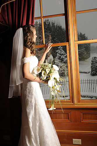 Bride looks out the window at winter landscape.