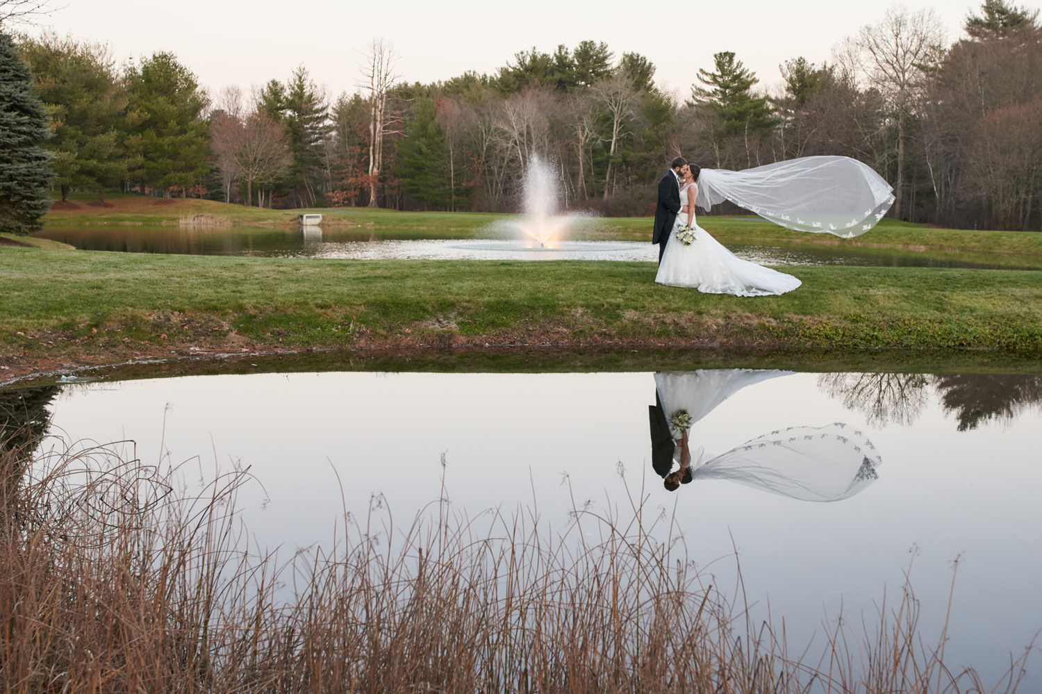 Bride and groom at Tewksbury Country Club with fountain and a slight breeze